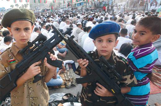 Libyan boys pose with toy guns as they gather during the first day of Eid al-Fitr near the courthouse in Benghazi, Libya, yesterday