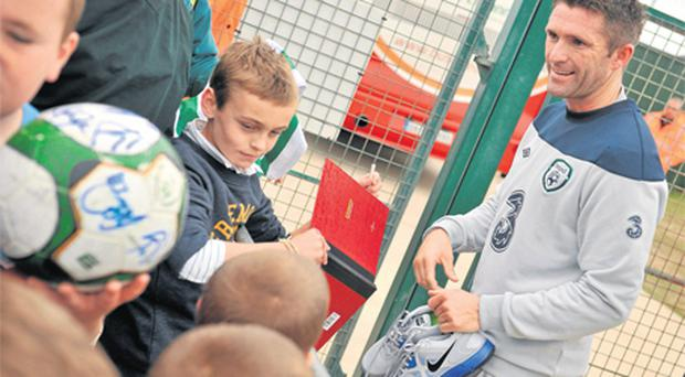 Ireland captain Robbie Keane signs autographs at the end of squad training ahead of the Euro 2012 Championship qualifier against Slovakia tomorrow
