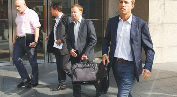 BP Russia president Jeremy Huck (right) leaves an office building housing a trading unit of British oil company BP in Moscow after bailiffs raided the oil company's offices in the Russian capital yesterday