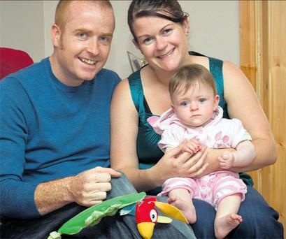 Leaving last year's trauma behind: Aisling and John McDonald with 13-month- old Sive, left, and on her first birthday,