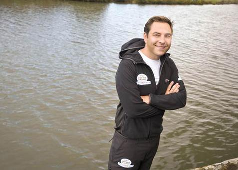 David Walliams stands on the bank of the River Thames before setting off on his attempt to swim the entire length of the river.