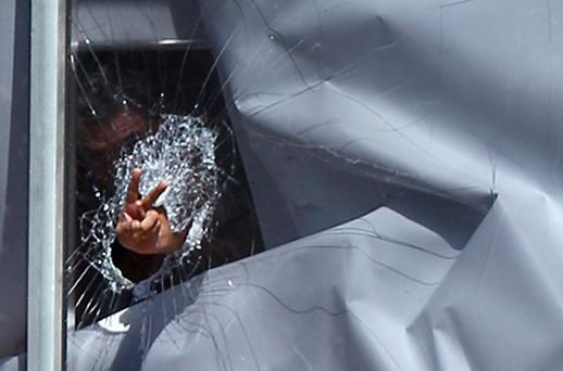 A man, believed to have strapped what appeared to be a bomb to himself, gestures after smashing a window next to the Parramatta court building near Sydney. Photo: Getty Images