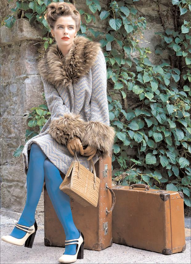 Wool coat with blue/cream herringbone pattern and faux-fur collar and cuffs, €138, and tan leather gloves with bows, €22, both Oasis; petrol-blue 70- denier tights, €8, and cream and black patent shoes, €60.50, both River Island;