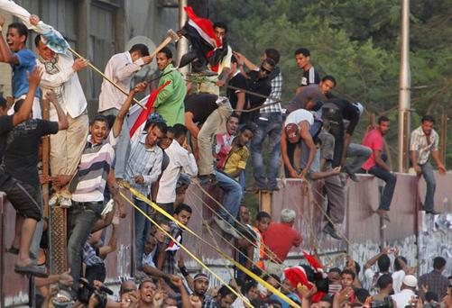 Hundreds of Egyptian activists demolish a concrete wall built around the Israeli embassy.