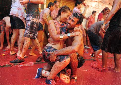 BUNOL, SPAIN - AUGUST 25: Revellers cuddle in tomato pulp during La Tomatina festival, the world's biggest tomato fight on August 25, 2010 in Bunol, Spain. More than 45000 people from all over the world descended on the small Valencian town to participate in this year's La Tomatina festival, with the local town hall estimating that over 100 tons of rotten and over-ripe tomatoes were thrown. (Photo by Jasper Juinen/Getty Images)