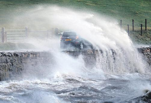 Spray from waves engulf a car at Strangford Lough