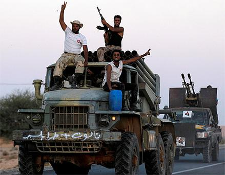 Anti-Gaddafi fighters cheer and shoot into air as they drive a multiple rocket launcher they captured from pro-Gaddafi forces. Photo: reuters