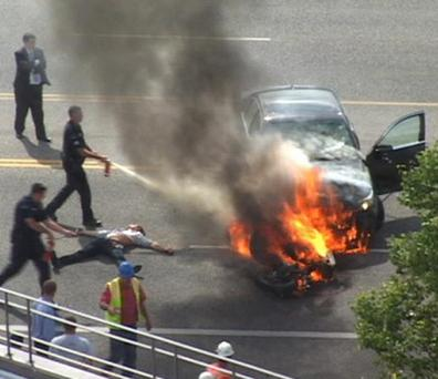 In this Monday, Sept. 12, 2011 image taken from video, police officers extinguish flames on a BMW and motorcycle that collided on U.S. 89 in Logan, Utah, as Brandon Wright lies on the ground between them. Wright was rescued by a group of strangers who tilted the BMW and pulled Wright, who was pinned underneath, to safety. Authorities said Wright was riding his motorcycle near the Utah State University campus in Logan when the 21-year-old collided with the BMW that was pulling out of a parking lot. Tire and skid marks on the highway indicate that Wright laid the bike down and slid along the road before colliding with the car, Assistant Police Chief Jeff Curtis said. (AP Photo/Chris Garff)