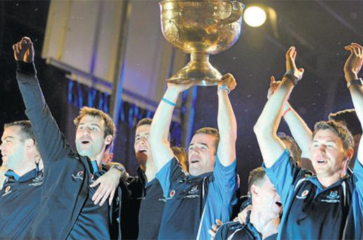 Dublin's Ger Brennan, flanked by his All-Irelandwinning teammates, including captain Bryan Cullen, left, and Eamon Fennell, right, lifts the Sam Maguire Cup to the rapturous cheers of 35,000 supporters who gathered at Merrion Square, Dublin, last night