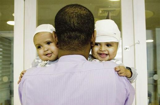 Success story: the separated twins, Rital and Ritag, with their father, Dr Abdelmajeed Gaboura