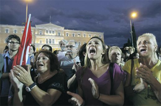 Protesters from the Greek trade union PAME shout slogans in front of the parliament in Athens yesterday during a rally against the government's plans for new austerity measures