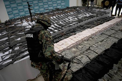 A Mexican marine stands in front of different kinds of firearms, cocaine and military uniforms seized from drug traffickers. Photo: Getty Images
