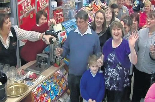 Annette Howard, left, fills up the glass of Martin McIntyre, as his wife Evelyn waves and daughter Sandra, in black, behind, celebrate yesterday at the EuroSpar shop in Belmullet, Co Mayo, where their winning ticket was bought on Friday. Photo: RTE