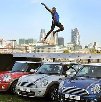 British long jumper JJ Jegede jumps over three special edition Mini cars at Potters Fields in London