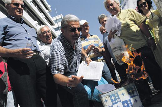 Pensioners burn bills for a new, one-off income tax in Athens, Greece, yesterday