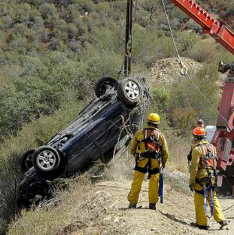 The car of a man who survived for five days after his car plunged 200 feet off a remote mountain is recovered in Castaic, California (AP)