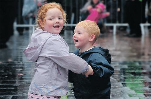 Olivia and Patrick Costin from Mayfield brave the rain at the Ceili Mor on Cork's Grand Parade yesterday
