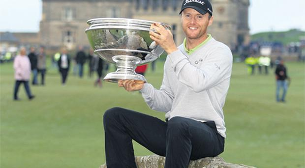 Michael Hoey sits on the Swilken Bridge at St Andrews after his victory in the Dunhill Links Championship yesterday