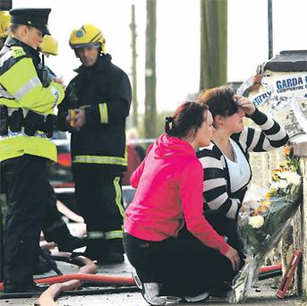 Teresa Kane, in the black and white top, placing flowers at the scene of the tragedy yesterday