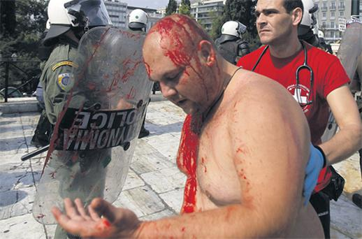 A paramedic helps a wounded protester during clashes in Athens yesterday