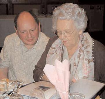 Maire looks through a family album with son-in-law Andrew Brody during her 80th birthday celebrations.