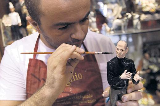 Artist Gennaro Di Virgilio paints a model figure of Apple founder Steve Jobs in his shop in Naples