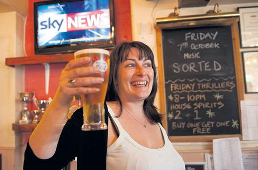 RAISING A PINT: English pub landlady Karen Murphy, originally from Cork, poses for photographs inside her pub in Portsmouth, England following her victory in a landmark battle with the English Premier League. Photo: Kieran Doherty