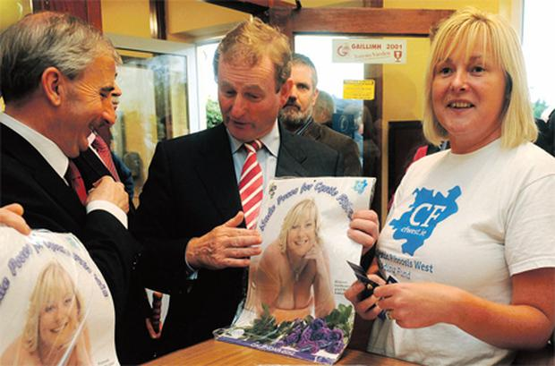 Cystic Fibrosis advocate Caroline Heffernan presents Taoiseach Enda Kenny and Presidential candidate Gay Mitchell with a copy of a charity nude calendar in aid of the western branch of Cystic Fibrosis Ireland