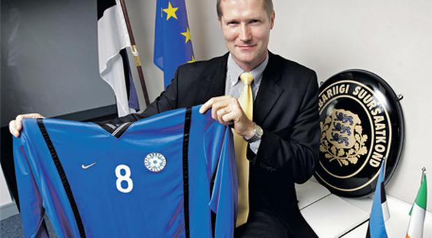 Estonian ambassador Mait Martinson proudly displays his national soccer jersey at his embassy in Dublin after the draw was made yesterday