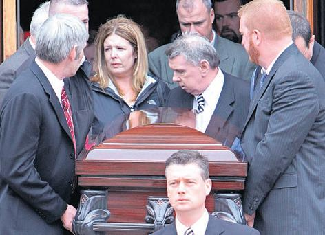 The casket of Ciaran O Conghaile is carried from Saint Mark's Church in Boston after his funeral yesterday
