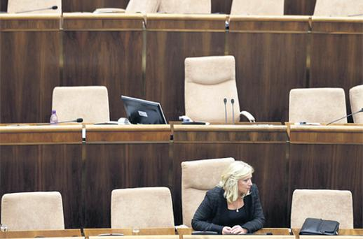Outgoing Slovak Prime Minister Iveta Radicova sits alone in the Parliament in Bratislava yesterday. Parliament ratified a plan to bolster the euro zone's EFSF rescue fund but she lost a confidence vote bringing on an early election as demanded by the opposition