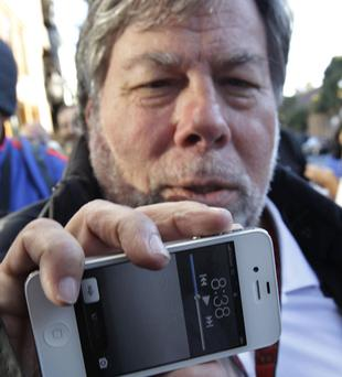 Apple co- founder Steve Wozniak holds up his new Apple iPhone 4S at the Apple store in Los Gatos