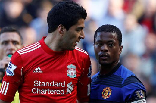 Liverpool's Luis Suarez (L) exchanges words with Manchester United's Patrice Evra (R) at Anfield