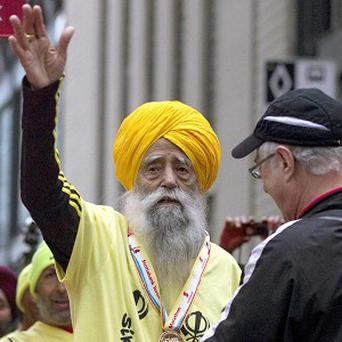 Fauja Singh, 100, receives a finishing medal after crossing the line in the Toronto Waterfront Marathon in Toronto (AP)