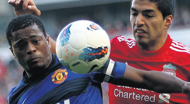 Patrice Evra is challenged by Luis Suarez during Saturday's Premier League clash at Anfield