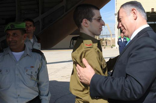 Freed Israeli soldier Gilad Shalit (C) is greeted by Israeli Prime Minister Benjamin Netanyahu (R) at Tel Nof Airbase. Photo: Getty Images