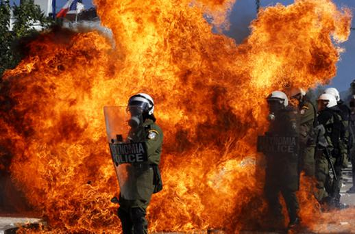 Protesters throw petrol bombs to riot police as they demonstrate in front of the Greek parliament in Athens on October 19. Photo: Getty Images