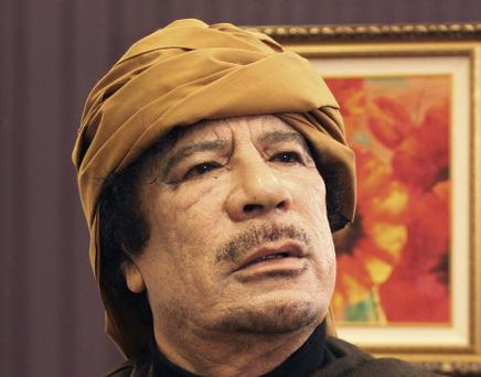 Libya's leader Muammar Gaddafi poses after an interview with TRT Turkish television reporter Mehmet Akif Ersoy at the Rixos hotel in Tripoli in this March 8, 2011 file photo. Deposed Libyan leader Gaddafi was captured and wounded near his hometown of Sirte at dawn on October 20, 2011 as he tried to flee in a convoy which NATO warplanes attacked, National Transitional Council official Abdel Majid said on Thursday. REUTERS/Huseyin Dogan/Files (LIBYA - Tags: POLITICS CIVIL UNREST HEADSHOT)