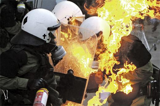 Riot policemen assist a colleague whose clothing caught fire after being hit by a petrol bomb during rioting in central Athens yesterday