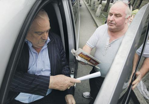 Tom McFeely, left, developer of Priory Hall, is issued with a legal notice on leaving the Four Courts after yesterday's High Court hearing. COLLINS
