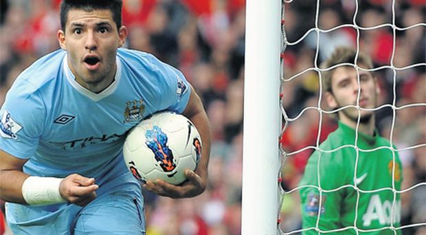 Manchester City striker Sergio Aguero celebrates his team's third goal as disconsolate United goalkeeper David de Gea looks on