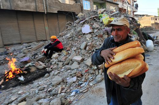 A Turkish man holds bread loaves as a rescue worker sits on rubbles from a damaged building after earthquake in the Ercis province of Van, in eastern Turkey. Photo: Getty Images