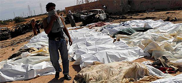 A man inspects bodies of Gaddafi loyalists after an attack on their convoy near Sirte