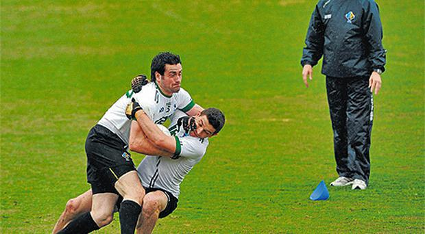 Kevin McKernan is tackled by his Ireland team-mate Eamonn Callaghan as coach Kieran McGeeney looks on at training in Melbourne yesterday