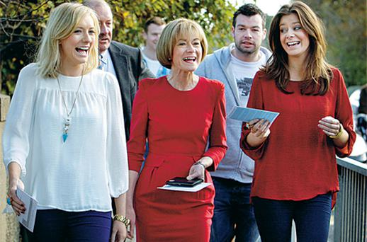 Mary Davis arrives in her famous red dress to cast her vote with daughters Emma and Rebecca