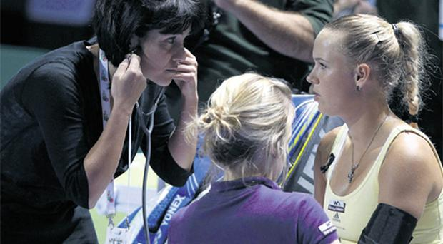 Caroline Wozniacki of Denmark has her blood pressure checked by a doctor during her WTA tennis championships match against Petra Kvitova of the Czech Republic in Istanbul yesterday