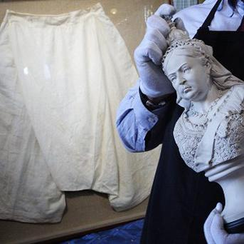 A staff member walks past a pair of silk bloomers which once belonged to Queen Victoria, which are to be auctioned in Edinburgh