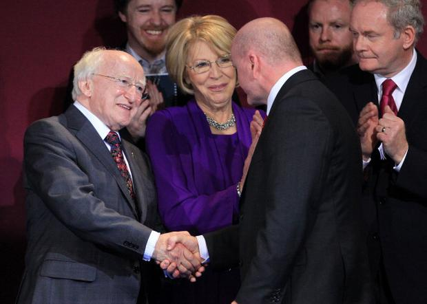 Newly elected Irish President Michael D Higgins (L) shales hands with his former rival Sean Gallagher (C) as Sinn Fein party's Martin McGuinness (R) looks on during the official announcement of the Irish presidential election's results at Dublin Castle in Dublin on October 29, 2011. Irish poet and human rights activist Michael D. Higgins was officially confirmed as his country's ninth president after a marathon two-day count. The 70-year-old former culture minister for the Labour party, the junior partner in the coalition government in Dublin, beat off a ex-IRA commander and a reality TV star to succeed Mary McAleese in the ceremonial post. AFP PHOTO/ PETER MUHLY (Photo credit should read PETER MUHLY/AFP/Getty Images)