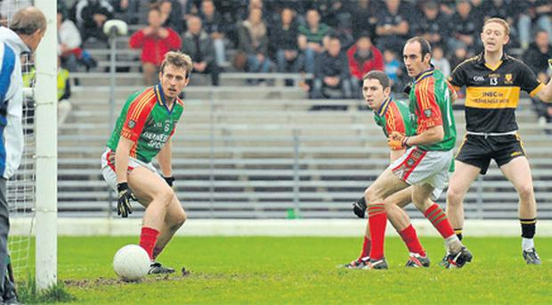 Mid Kerry's Donnchadh Walsh can only look on as a shot from Dr Crokes star Colm Cooper (far right) trickles into the net in the first minute of yesterday's county final