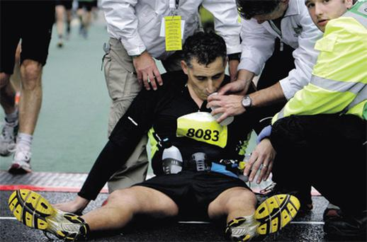 Jim Hickey, from Barna, Co Galway, gets a little help after crossing the finish line in the Dublin marathon yesterday